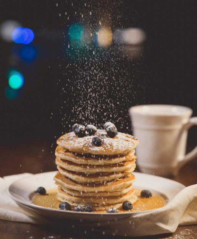 Sprinkling powdered sugar on pancakes